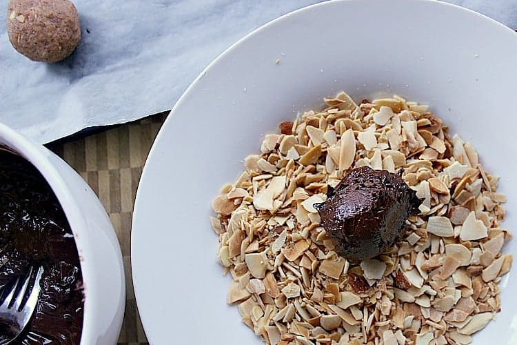 low carb truffle coated in chocolate and in a pile of slivered almonds.