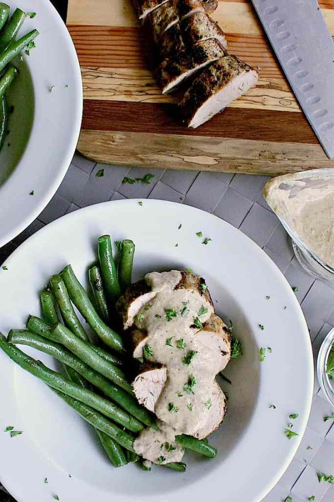 Sliced pork tenderloin next to fried green beans and covered in keto mushroom sauce.