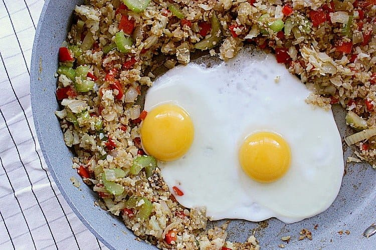 Cauliflower fried rice moved to the sides of the skillet with two cracked eggs in the middle.