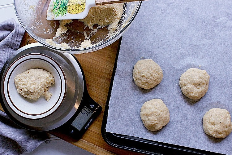Measuring out buns using a scale. Four portions of batter shaped into balls and placed evenly on a baking sheet.