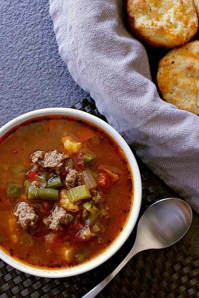 Bowl of low carb hamburger soup next to a bowl of low carb biscuits.