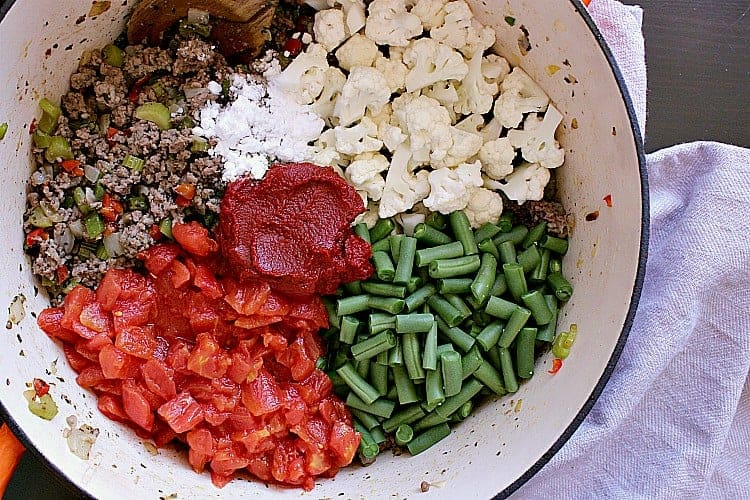Cooked veggies and ground beef with chopped cauliflower, green beans and tomatoes on top.
