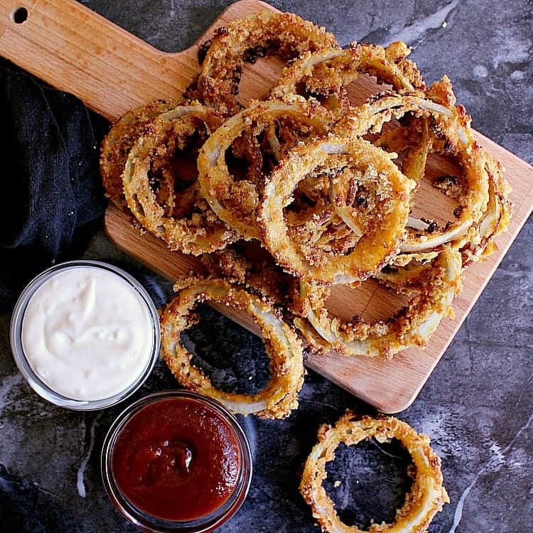 Pile of low carb onion rings next to a dish of ketchup and another dish of garlic aioli.