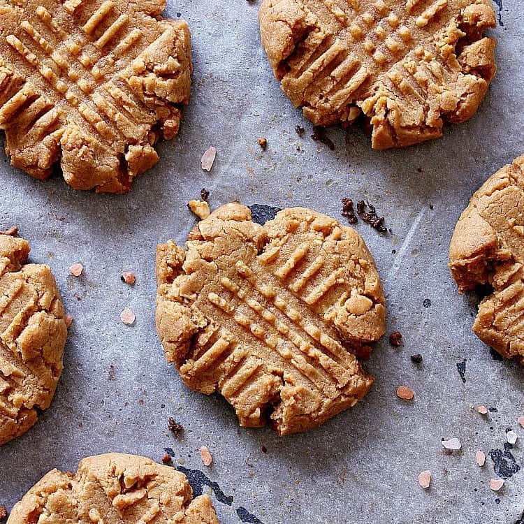 Low carb peanut butter cookies cooling on a baking sheet with parchment paper.
