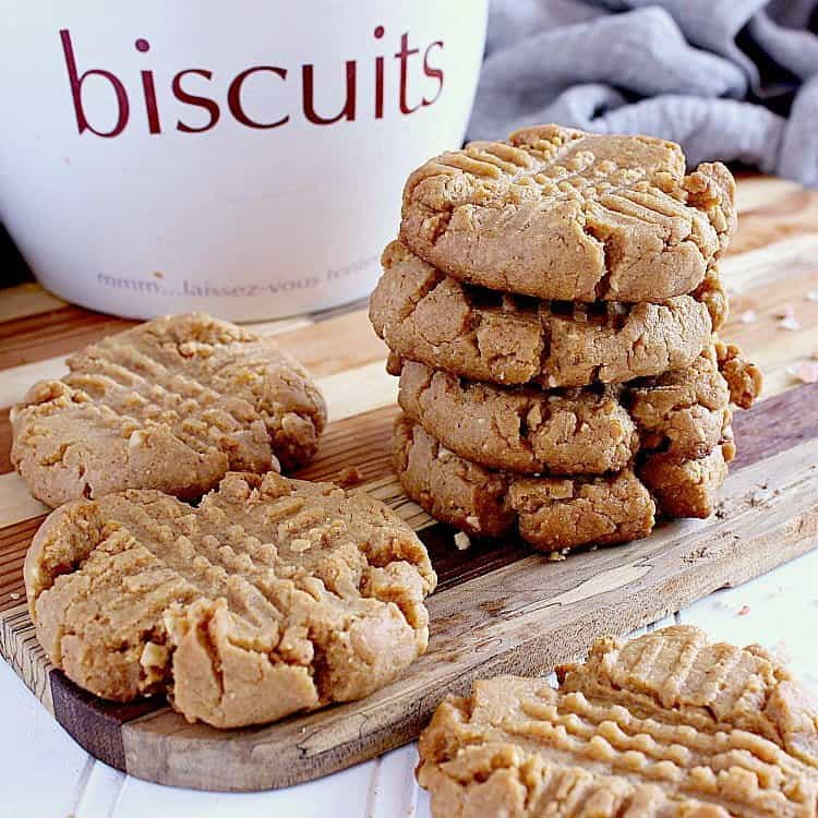 Stack of low carb peanut butter cookies next to a cookie jar.
