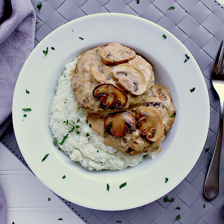 Plate with mashed cauliflower, two salisbury steaks and covered in mushroom sauce.