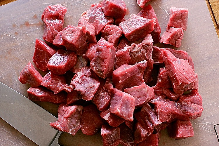 """Cutting board with chuck roast cut into 1-2"""" pieces."""