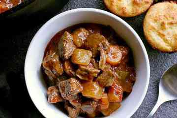 Bowl of low carb beef stew next to the pot of stew and some low carb biscuits.