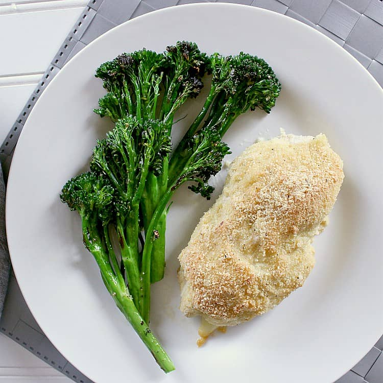 Plate with chicken cordon bleu and garlic sautéed broccolini.