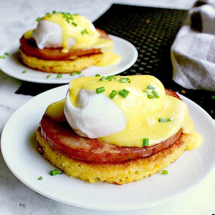 Two plates each with a keto eggs benedict and garnished with chives.