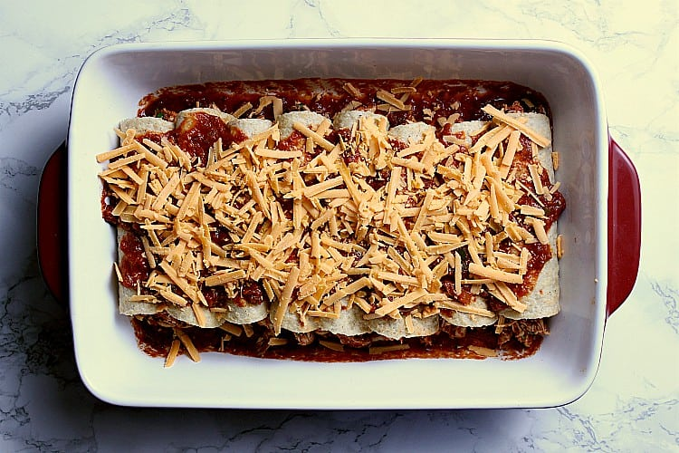 baking dish filled with keto enchiladas and covered in sauce and cheddar cheese.