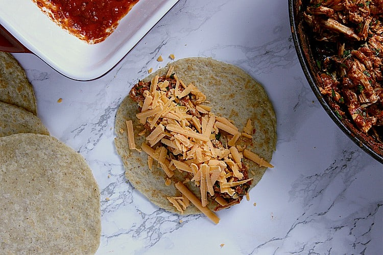 Almond flour tortilla with chicken mixture and shredded cheese.