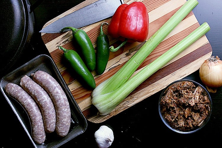 Cutting board with celery, peppers, pulled pork, sausages, garlic and onion.
