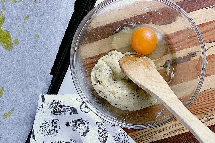 Keto flatbread dough with a cracked egg.