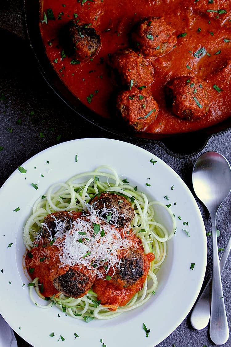 Cast iron skillet with cooked meatballs, hot marinara sauce, beside a bowl of zoodles, meatballs and parmesan cheese.