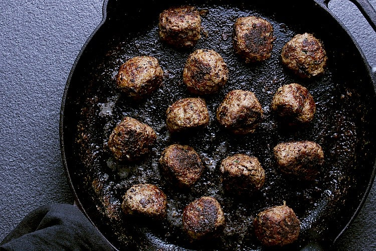 Balls all cooked in a cast iron skillet, ready for the sauce.