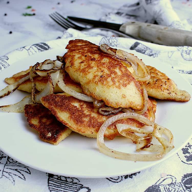 Plate with fried Keto Pierogies and onion.