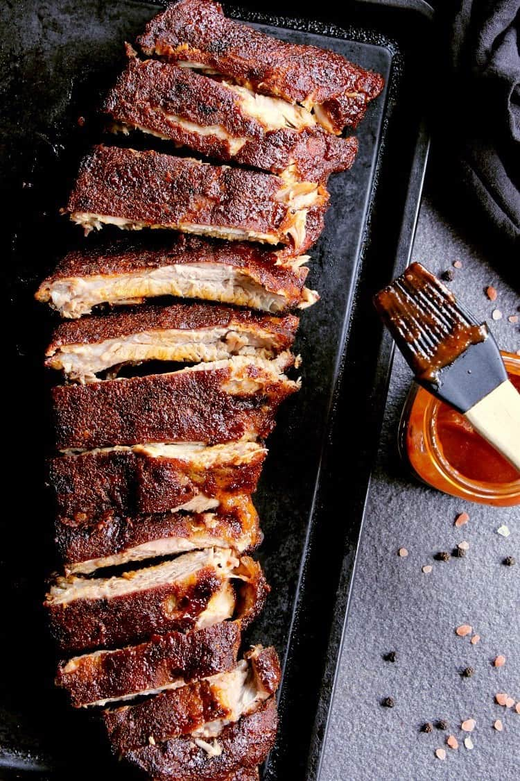 Baking sheet with fully cooked ribs, cut into sections.