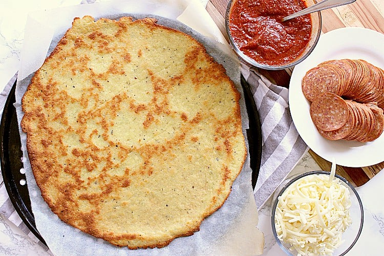 Baked Fathead Pizza Crust next to dishes with pizza sauce, mozzarella and pepperoni.