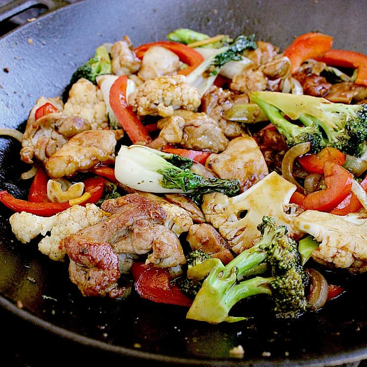 Cast iron skillet filled with Keto Chicken Stir Fry, ready to be served.