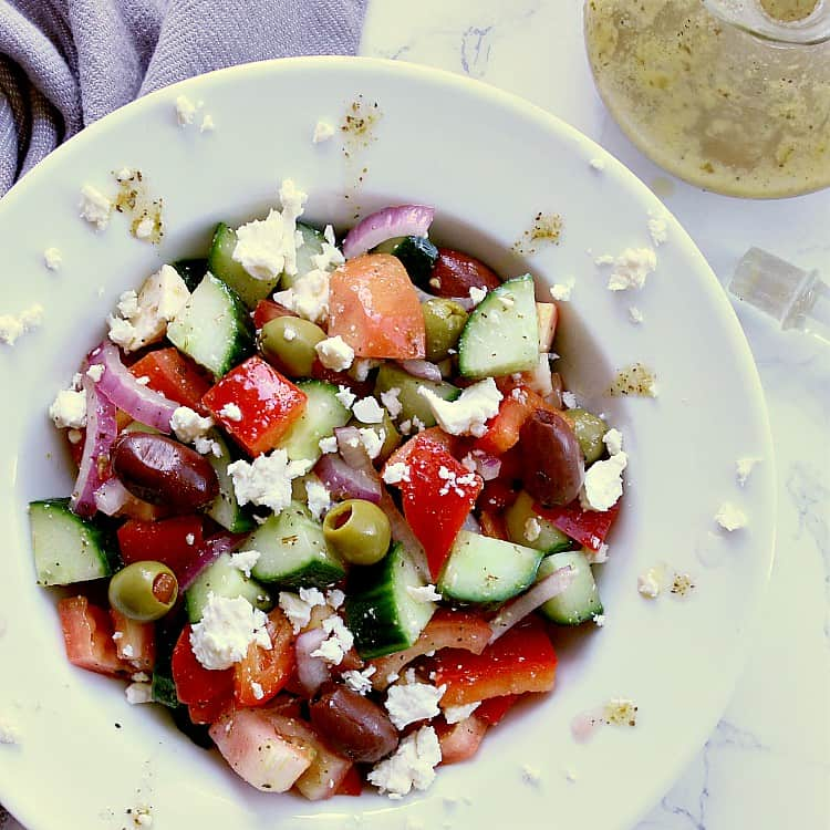 White bowl with greek salad which has been tossed in the keto dressing. A jar of the dressing is beside the bowl.