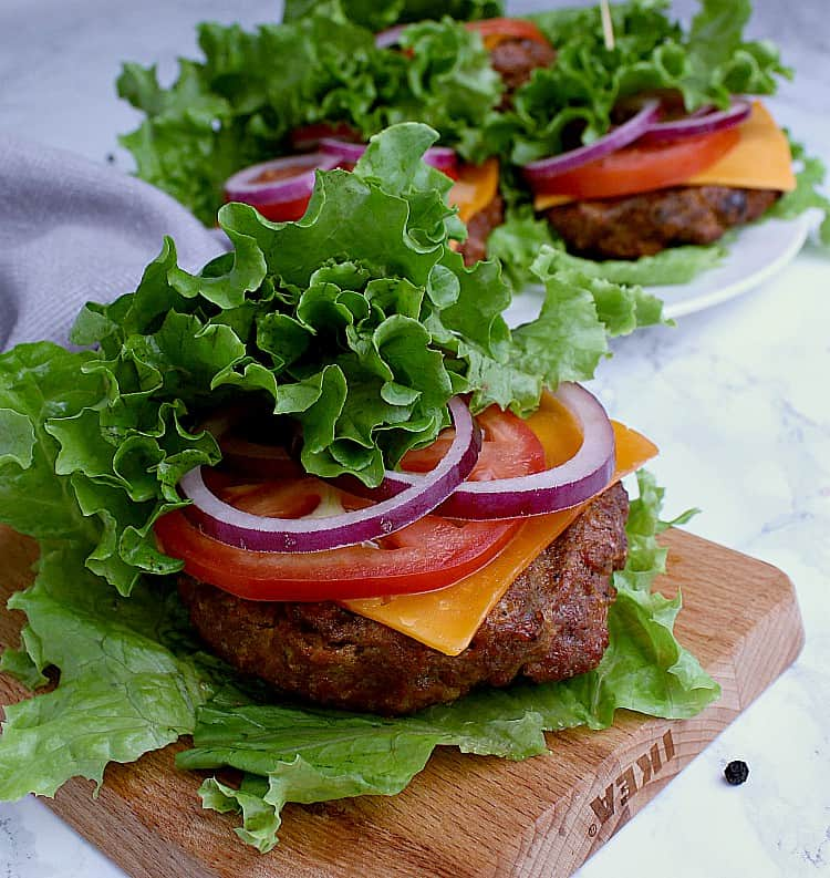 Four Keto Burgers wrapped in leaf lettuce along with cheese, tomato and red onion.