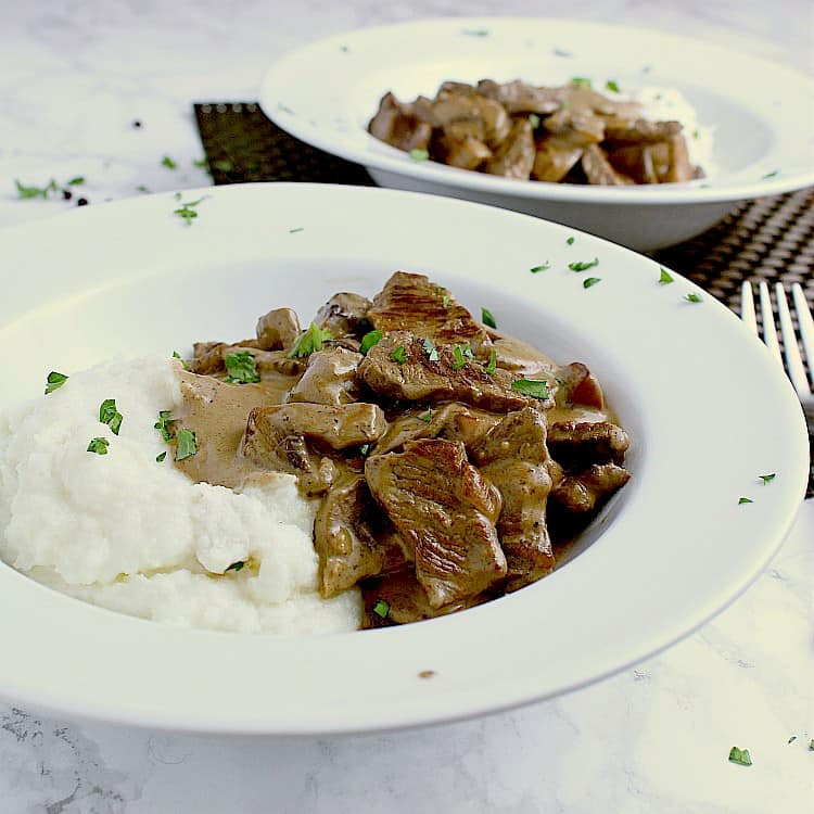 Two white bowls with cauliflower mash, keto beef stroganoff and garnished with fresh parsley.