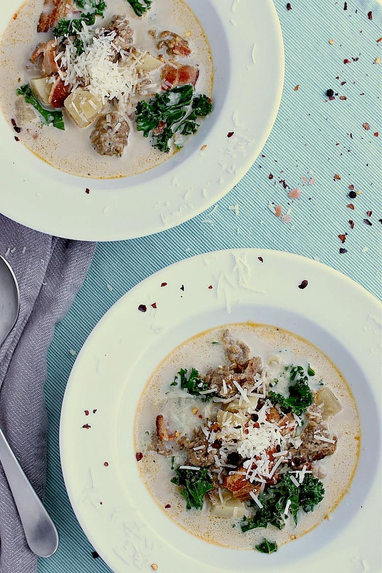Two white soup bowls filled with keto zuppa toscana and garnished with grated parmesan cheese.