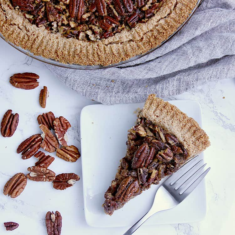 One slice of Keto Pecan Pie on a white plate with a fork, with the full pie beside.