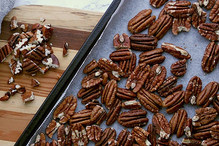 Roasted pecans on a baking sheet beside some chopped pecans.