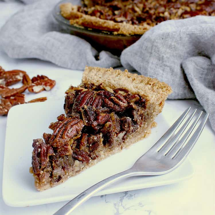 One slice of Keto Pecan Pie on a white plate with a fork, with the full pie behind.