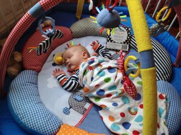 Lydia asleep on the play gym