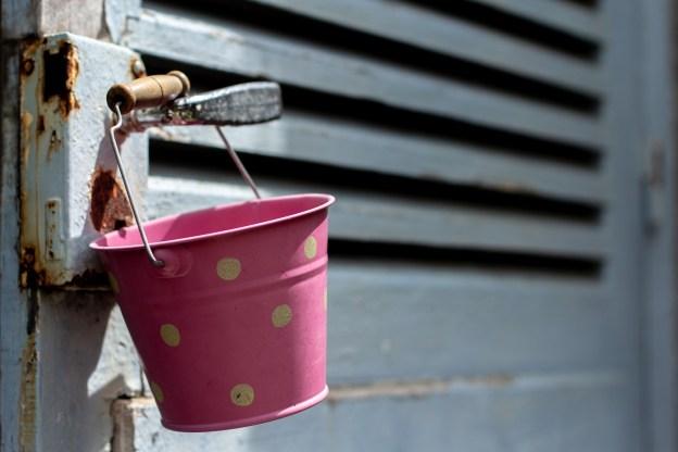 rostiger rosa Eimer hängt an einer verrosteten Tür