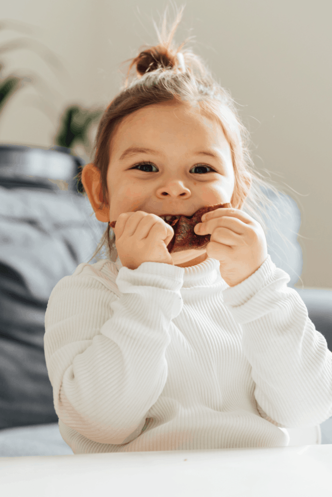 toddler girl with a smile eating a granola bar at a table