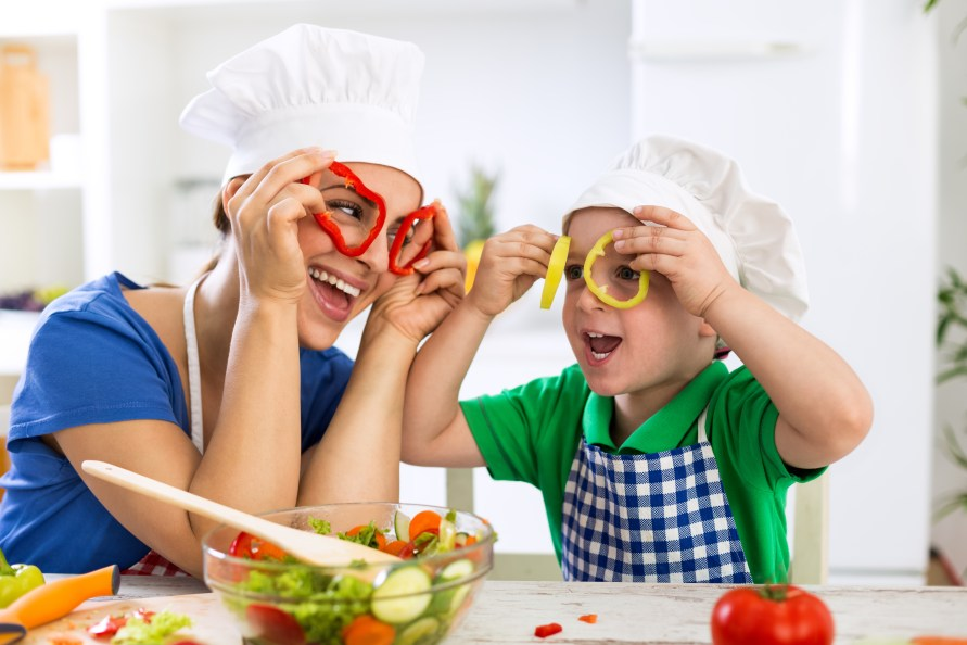 Happy family playing with vegetables in kitchen at home