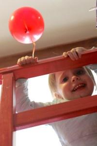 Mini Puce s'amusant avec un ballon de plastique dans une tour de bois...