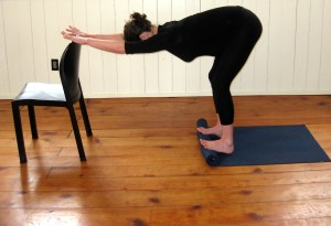 standing forward fold with rolled mat and chair prenatal yoga