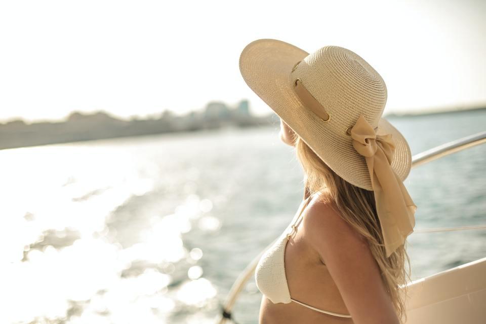 femme sur un bateau s'expose au soleil huile solaire