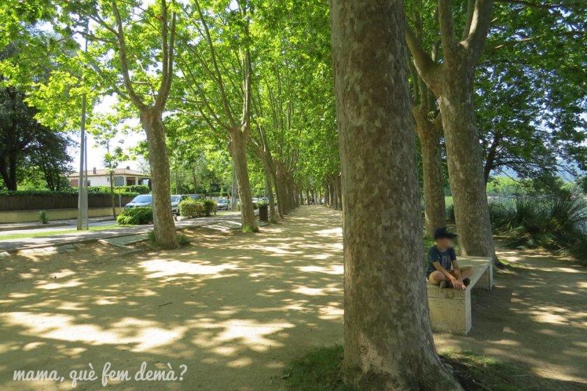 un niño sentado en un banco en el paseo del lago de banyoles