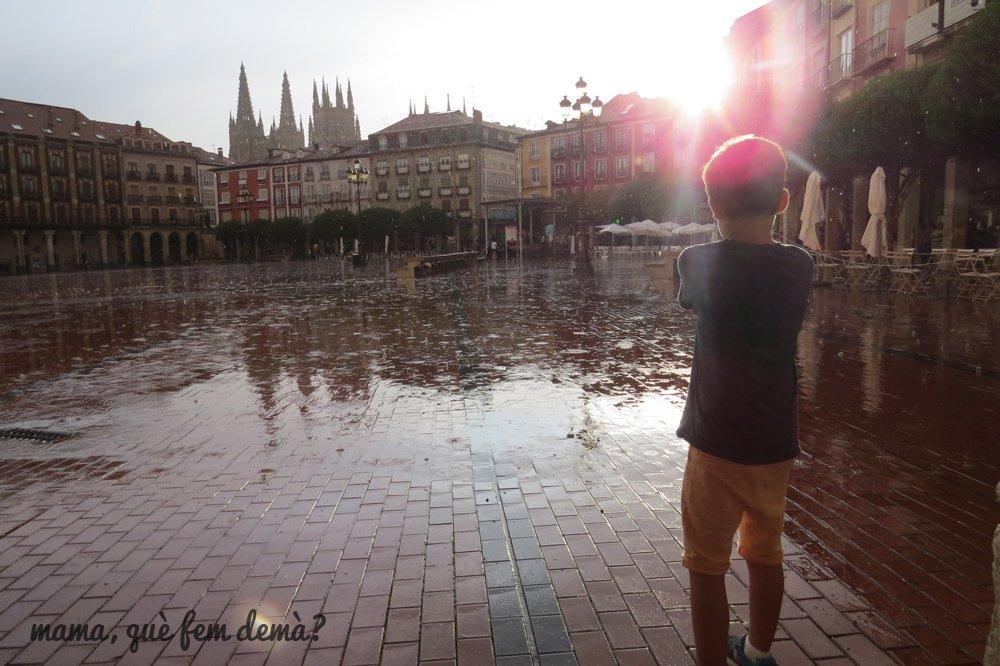 niño mirando la lluvia en la plaza mayor de Burgos
