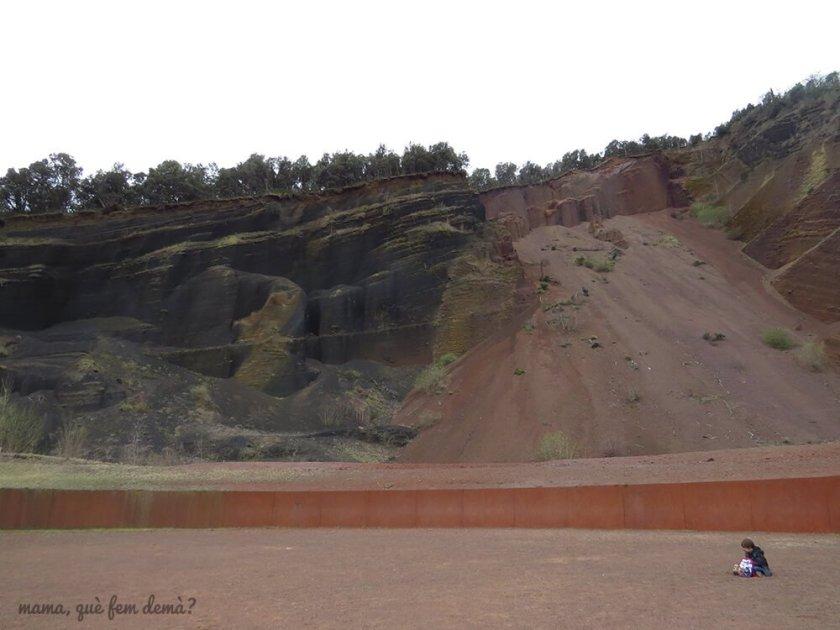 Explanada de tierra volcánica en el Croscat, con un niño sentado en medio