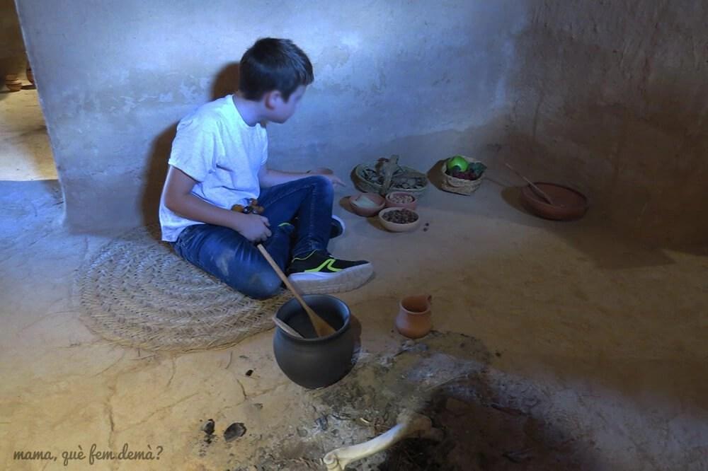niño dentro de una recreación de una casa ibérica en el Poblat ibèric Ca n'Oliver de Cerdanyola del Vallès