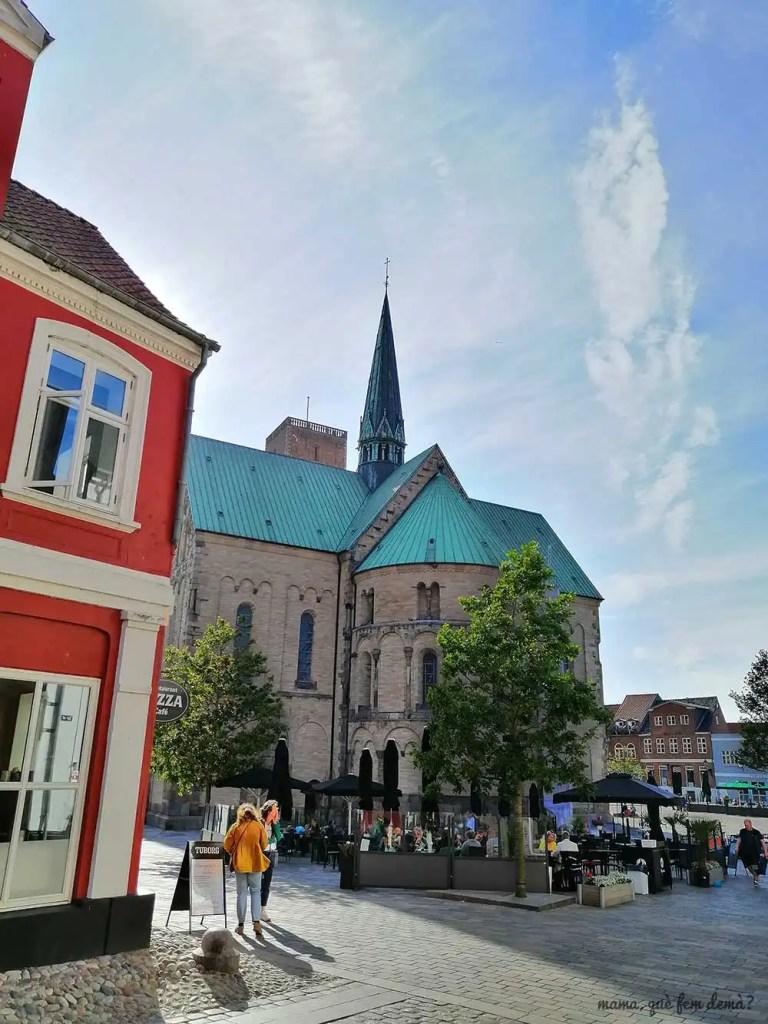 Parte trasera de la catedral de Ribe, rodeada de bares con terraza