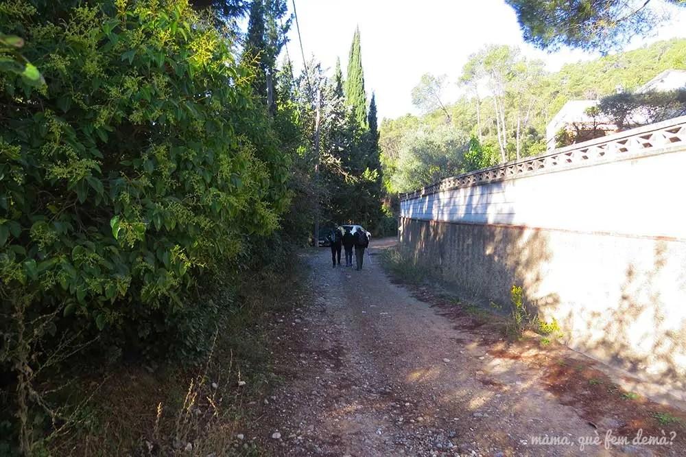 Pista de tierra entre casas al final de la avenida Can Castellví que lleva a la cascada de la Rierada