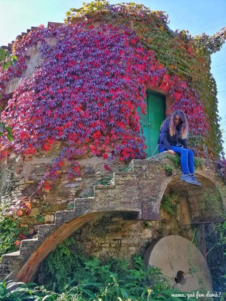 Mujer sentada en las escaleras de piedra del molino que hay delante de la Masia Can Planes de Molins de Rei