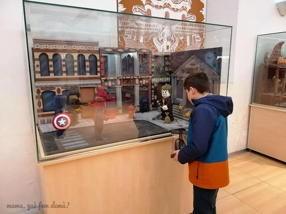Niño mirando una gran mona de super héroes de Lego en el Dos huevos de Pascua decorados y metidos en sus cajas de cartón en el Museu de la Xocolata de Barcelona