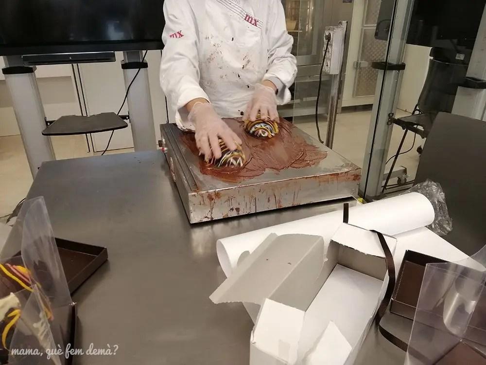Chica calentando las dos mitades de los huevos de Pascua en el Museu de la Xocolata de Barcelona