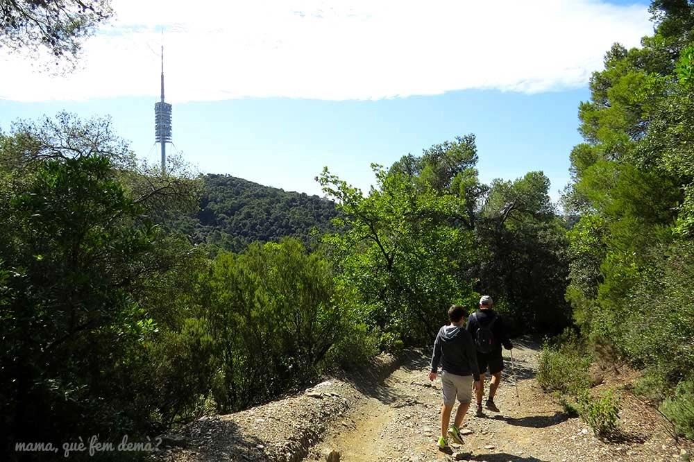 Dos personas caminando por la serra d'en Cardona, con la Torre de Collserola a lo lejos