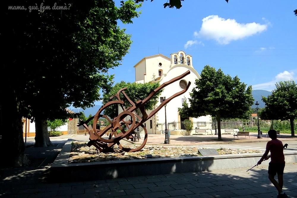 Niño delante de la escultura en forma de carro delante de la ermita del remei de Santa Maria de Palautordera