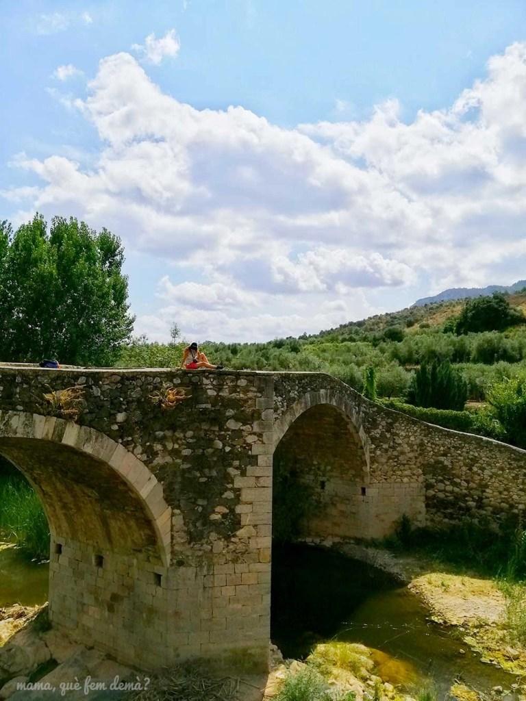 Mujer sentada en el puente medieval de la Vilella Baixa